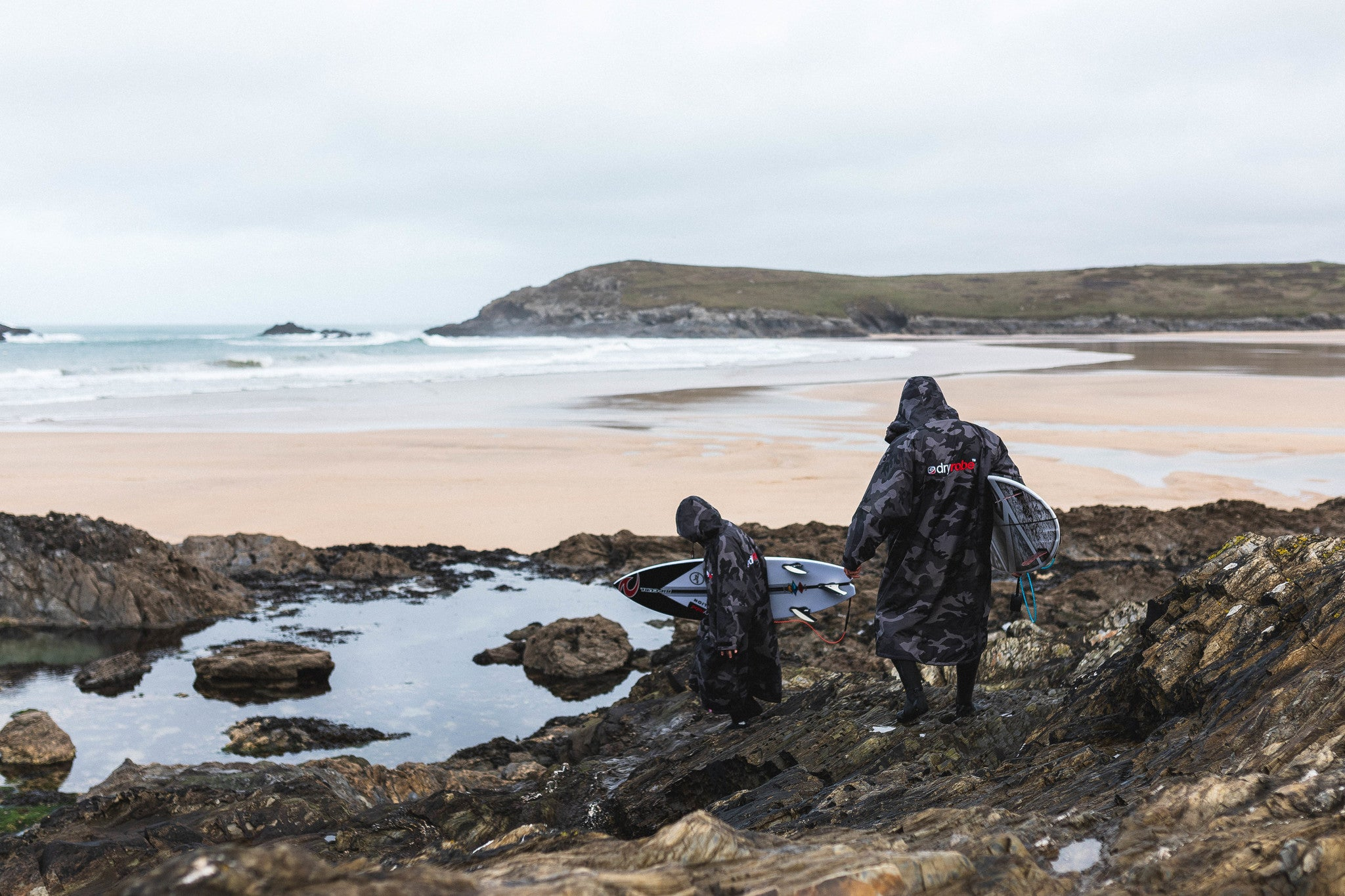 Ben and Lukas Skinner walking to the beach carrying surfboards whilst wearing dryrobe Advance Change Robes