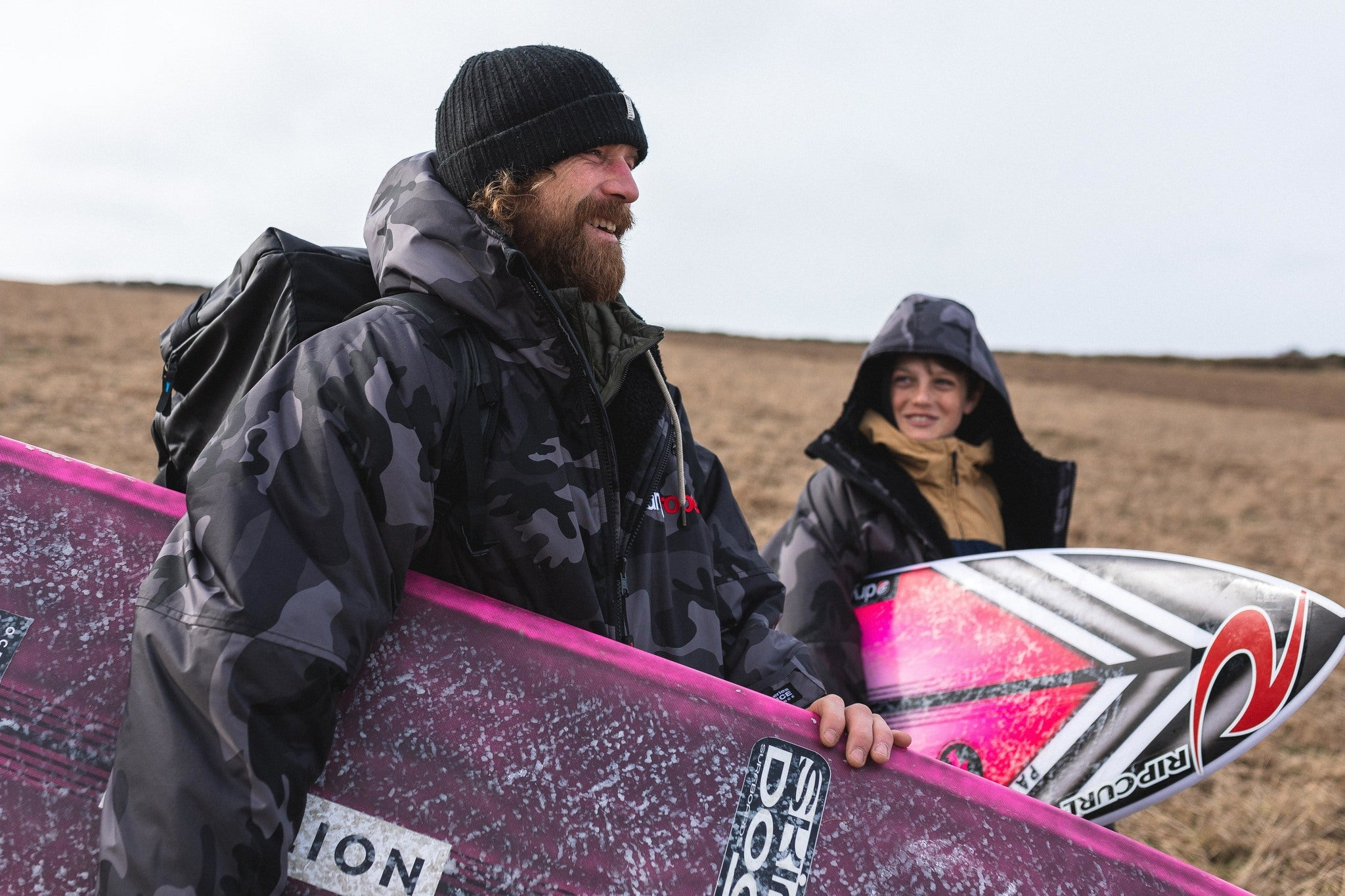 Ben and Lukas Skinner wearing Black Camo dryrobe Advance change robes whilst carrying surfboards