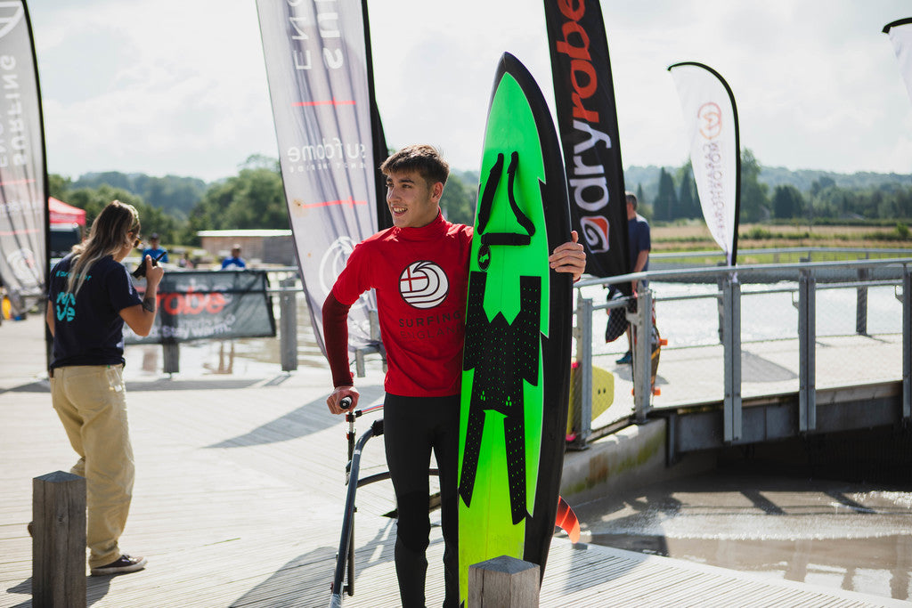Competitor getting ready to to get into the water at the 2021 dryrobe English Adaptive Surfing Open