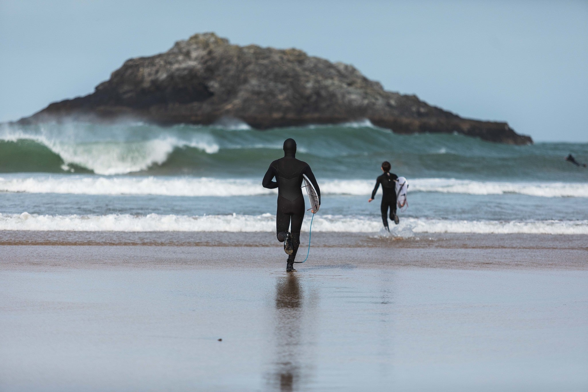 Lukas and Ben Skinner running into the sea wearing wetsuits and carrying surfboards