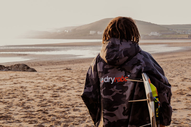 Siyanda Hewitt holding a surfboard and looking at the sea in Croyde