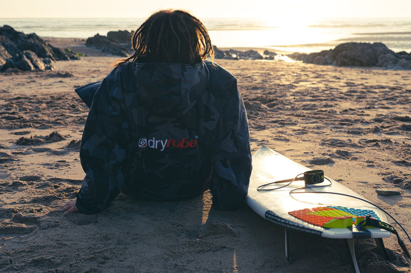 Siyanda Hewitt sat on the beach looking at the sunset with his surfboard