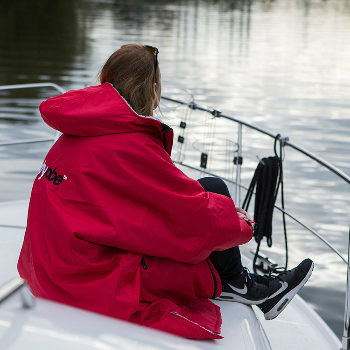 1| dryrobe Advance Long Sleeve Red Grey Female on Boat Lifestyle Image