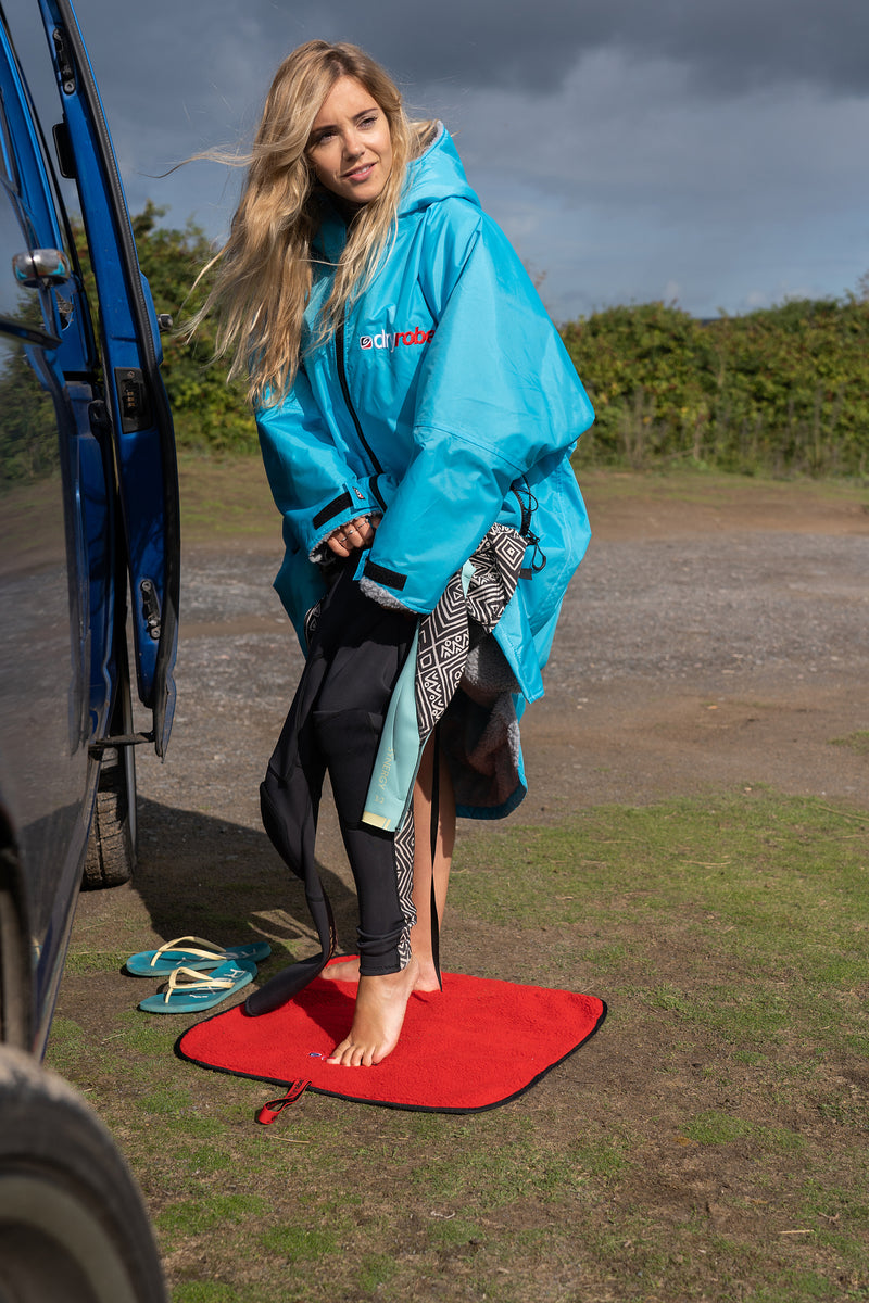 Getting changed on a dryrobe Changing Mat in Black & Red