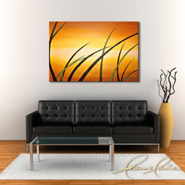 Leanne Laine Fine Art painting displayed above couch of abstract grass landscape against sunrise orange sky