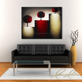 Leanne Laine Fine Art original artist painting displayed above couch of glowing red trees on abstract landscape