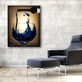 Leanne Laine Fine Art painting displayed above chair of woman in blue wine blowing a kiss in pouring wine from a bottle