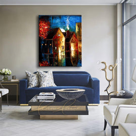 Leanne Laine Fine Art painting displayed above couch of night time sky with lights on in houses by red tree glowing and reflecting on street