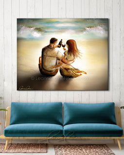 Leanne Laine Fine Art original artist painting displayed above couch of romantic man and woman on tropical beach by water waves enjoying wine in bottle and glass