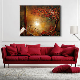 Leanne Laine Fine Art painting displayed above couch of autumn fall red and yellow tree with leaves pouring out of a wine glass