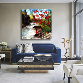 Leanne Laine Fine Art original artist painting displayed above couch of woman in red dress and hat standing by river with red yellow and green trees