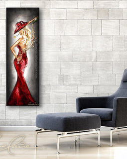 Leanne Laine Fine Art painting displayed above chair of sexy woman in red hat and red dress pouring white wine behind back with rose in mouth