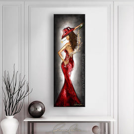 Leanne Laine Fine Art painting displayed above table and vase of sexy woman in red hat and red dress pouring white wine behind back with rose in mouth