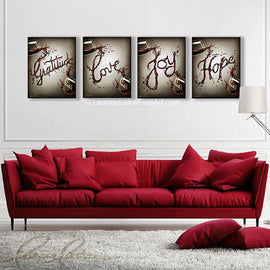 Leanne Laine Fine Art original artist painting displayed above couch of red and white wine splashing and spelling words gratitude love joy and hope between glasses