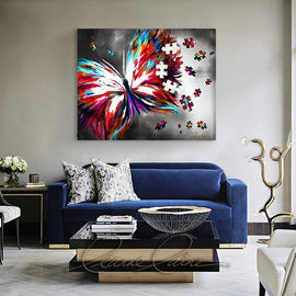 Leanne Laine Fine Art original artist painting displayed above couch of beautiful turquoise spring butterfly flying with puzzle pieces for autism awareness