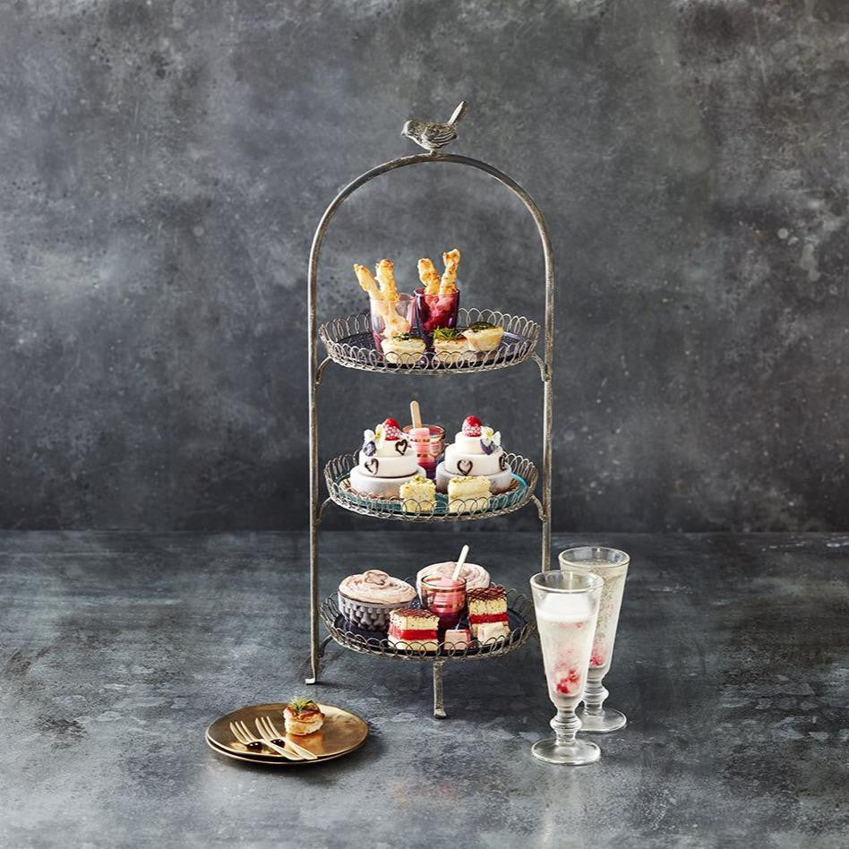 Ice Cream Afternoon tea display of different cakes and savoury items, with two glasses of prosecco