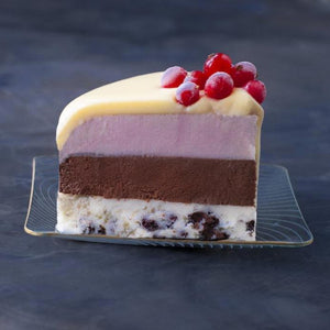 A slice of ice cream cake covered in white chocolate ganache decorated with redcurrants