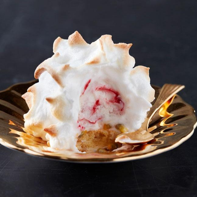 An individual baked alaska on a golden plate with a golden spoon. The central ice cream is raspberry ripple