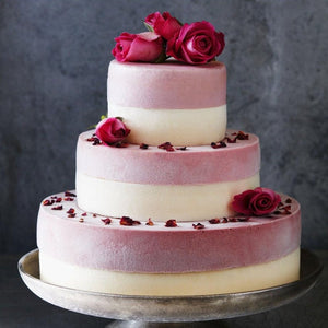White and pink three tiered ice cream wedding cake decorated with fresh roses