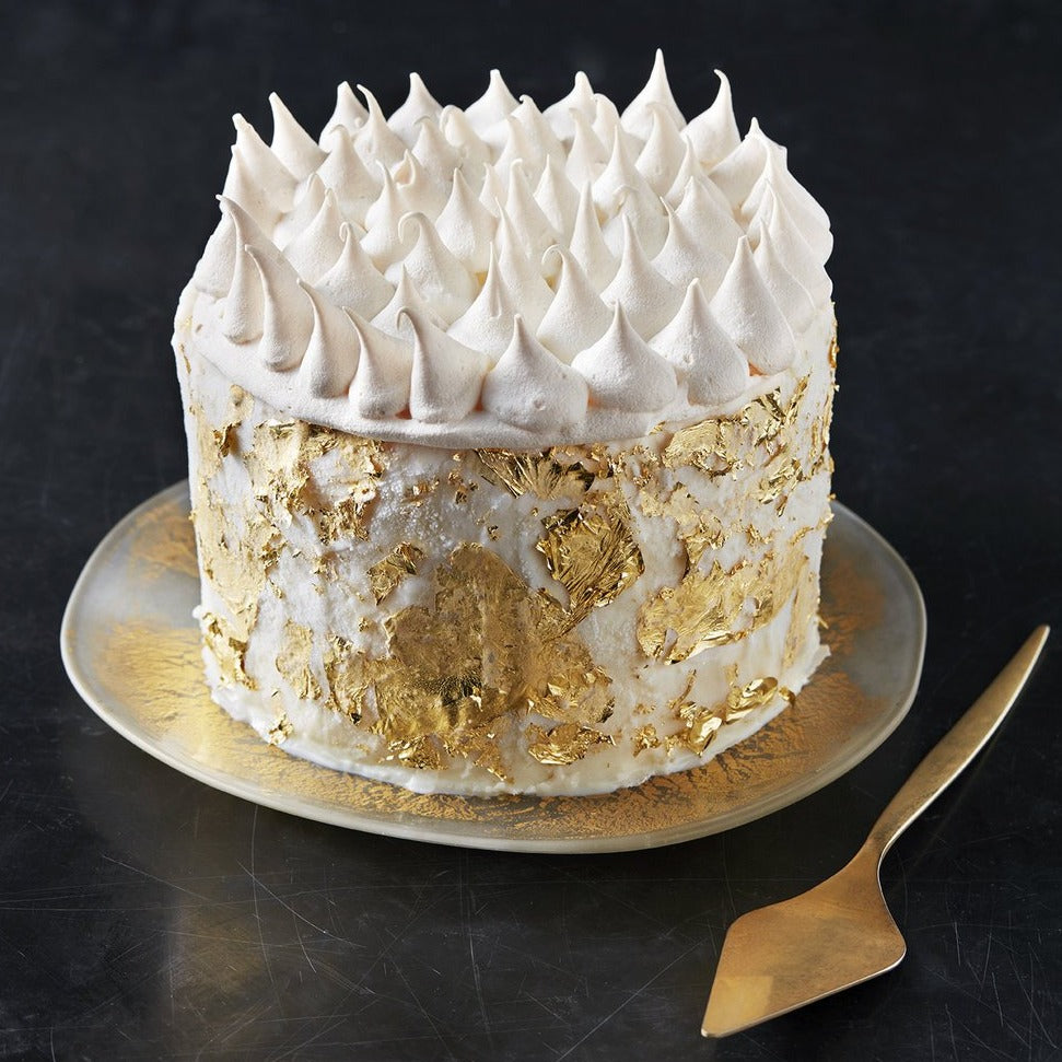 A tall ice cream cake encrusted with gold leaf and topped with meringue peaks on a golden tray