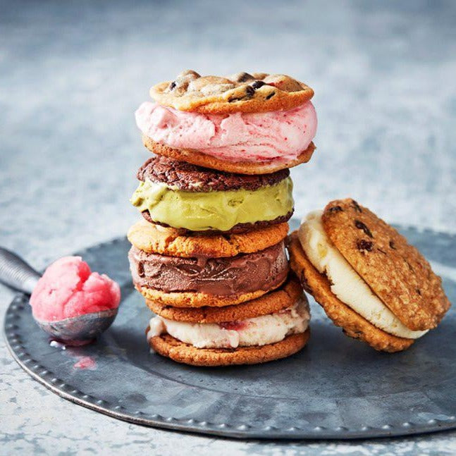 A pile of colourful ice cream sandwiches on a silver tray with a scoop of pink sorbet