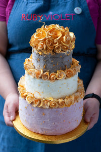 A birthday cake with three tiers of ice cream decorated with golden roses