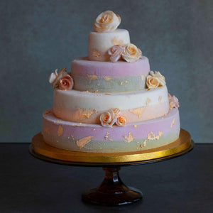 Four tiered ice cream wedding cake decorated with gold foil and roses