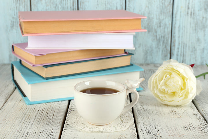 a pile of pastel colored books, a rose and a cup of tea