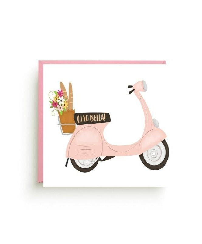 Light pink Vespa with a basket on the back carrying a bouquet of flowers and a baguette.  Text on the seat that reads