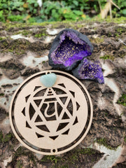 Tree trunk with on top our wooden heart chakra symbol and Purple Quartz Geode