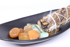 Golden healer quartz and Chrysoprase in a black dish with a sage smudging stick