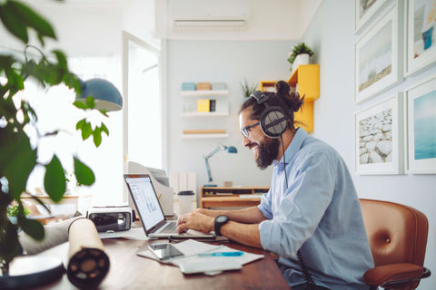 man sat at desk working from home and smiling