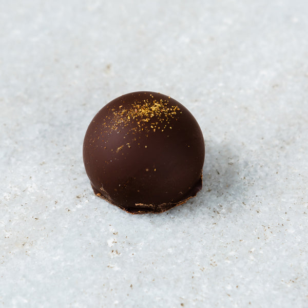 Tempered Chocolate cassis truffle topped with hibiscus powder..