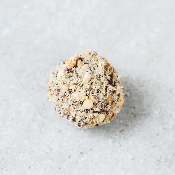 Tempered coffee walnut truffle covered in chopped walnuts.
