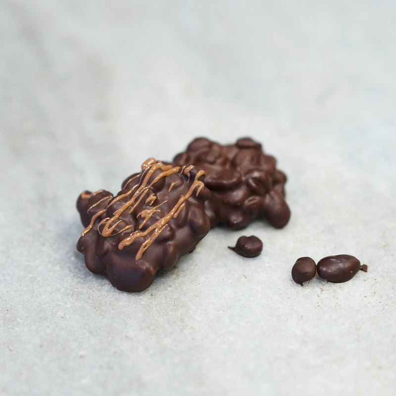 Bunches of Tempered chocolate-covered expresso beans and drizzled with light milk chocolate on top.