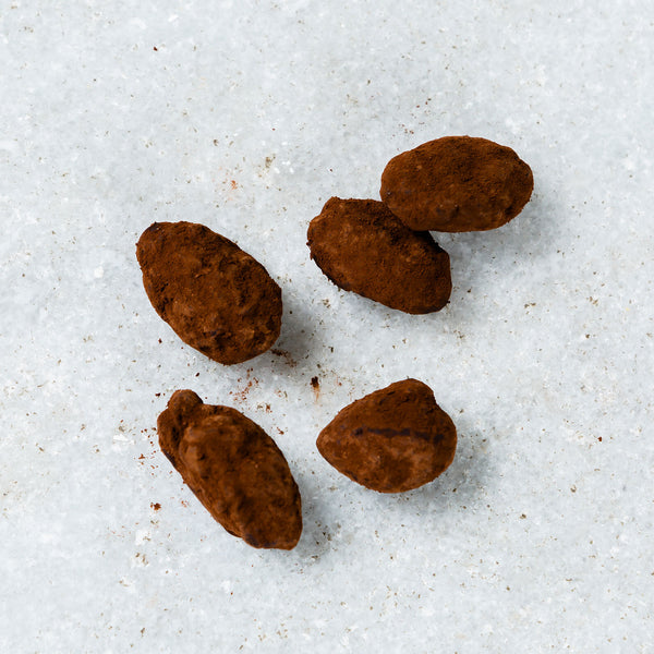 Individual roasted almonds covered in hazelnut chocolate and cocoa powder.