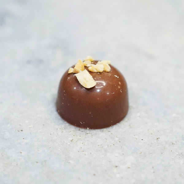 Milk chocolate Tempered peanut butter truffle topped with chopped peanuts.