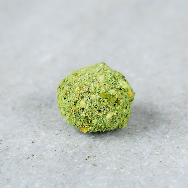 Tempered dark chocolate pistachio matcha truffle topped with chopped pistachios and green matcha powder.