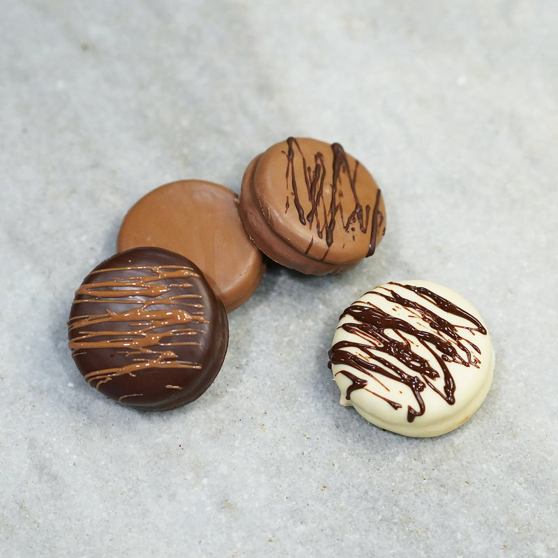 Cream-filled sandwich cookies dipped in Tempered milk, dark and white chocolate. Drizzled with chocolate on top.