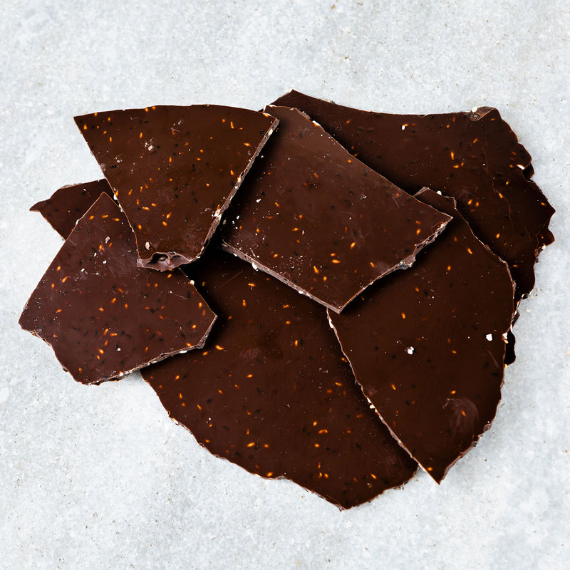 Thin, Tempered dark chocolate glass with toasted white and black sesame seeds incorporated throughout.
