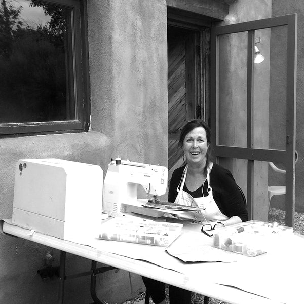 Darcy Falk at her sewing machine outside a Taos studio