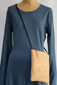 Cork cross body bag with hand-stamped, patinated brass tag on mannequin