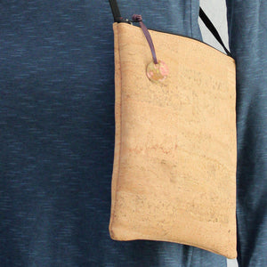Detail of Cork cross body bag with hand-stamped, patinated brass tag
