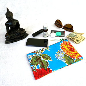 Small turquoise oilcloth pouch with items that could fit inside of it. Sunglasses, facial toner spray, contact lens case, cell phone, credit card, lipstick, cash