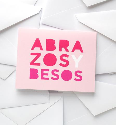 "Pink card reads ""Abrazos Y Besos"""