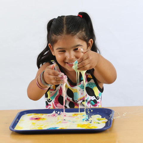 Little girl plays with colorful oobleck from the Crazy Colors Messy Play Kit.
