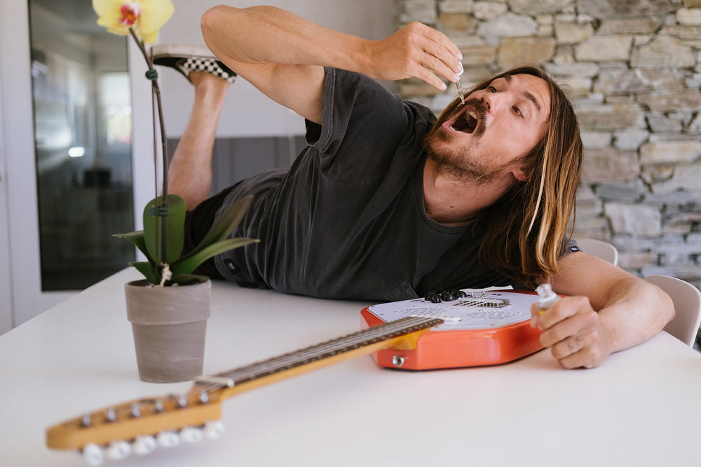 Surfer dude taking some InnerG orangesicle CBD hugging a guitar laying on a table.