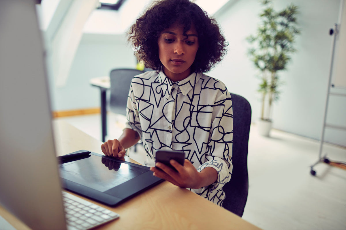 Young professional woman checking her phone while drawing on a tablet