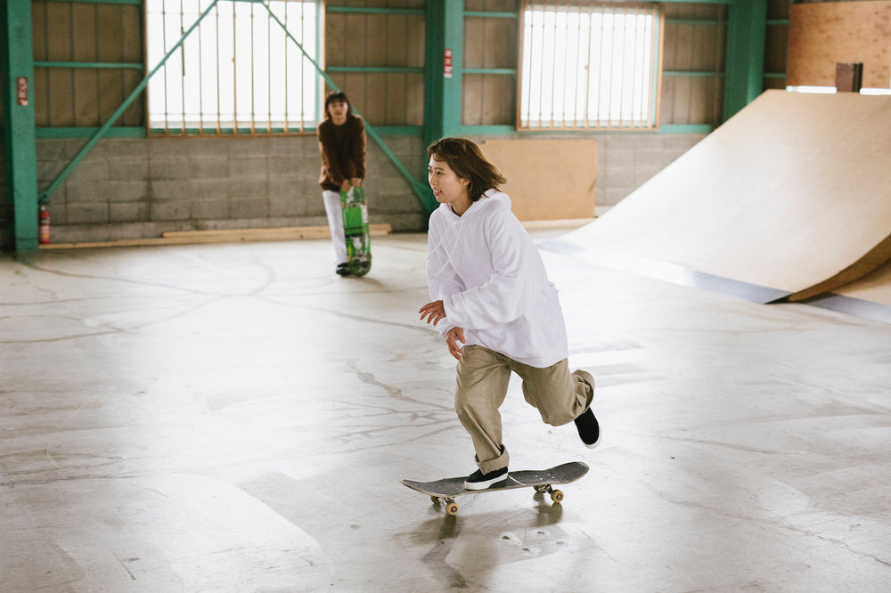 Two women skateboarding at a skatepark