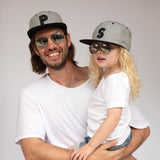 father and son in sunglasses and caps matching